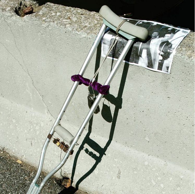 A walking crutch leaning on a large black and white photo of the Obamas, which is resting on top of a concrete barrier on the side of a street. A rosary necklace is wrapped around the handgrip and the shoulder rest of the crutch. Found in South Williamsburg, New York City.
