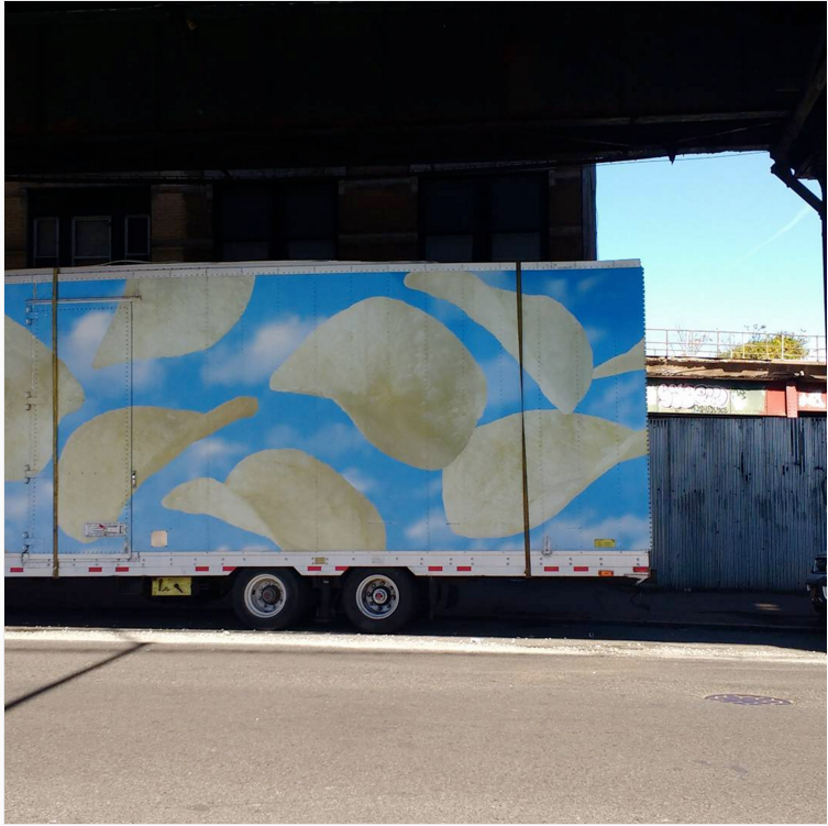 Semitruck with vinyl decoration on side that depicts potato chips floating in mid-air. Seen outside Devin's old apartment in Brooklyn.