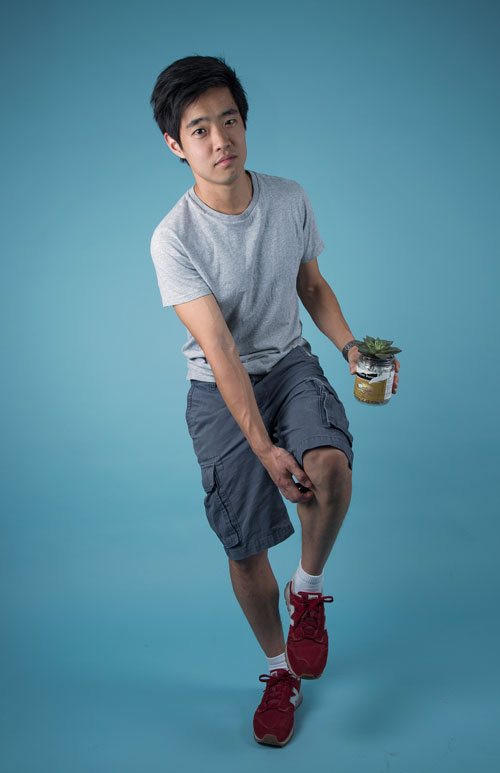 Photo of Albert scratching knee while holding succulent.