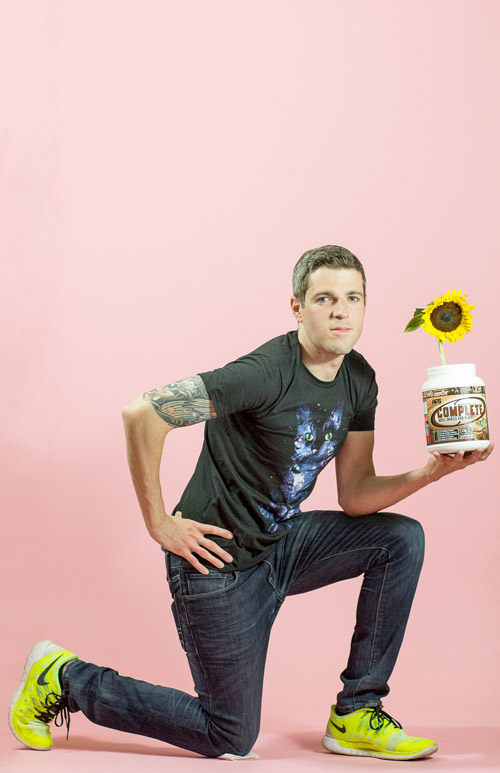 White man on pink background in sprint position holding protein jar with sunflower in it