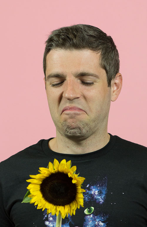 Photo of Brad frowning at sunflower