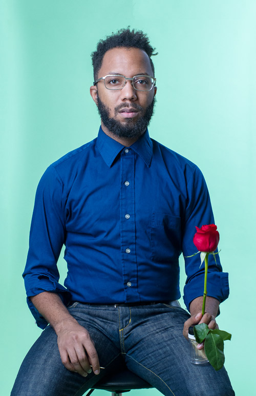 Young black man looking to the side, holding rose with green background