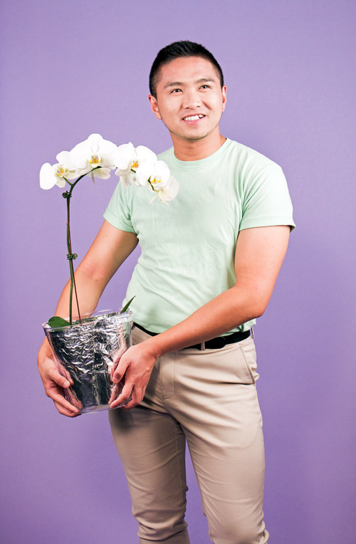 Photo of JJ standing with a potted orchid in an ice bucket.