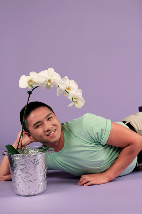 JJ lying down with head on hand next to an orchid.